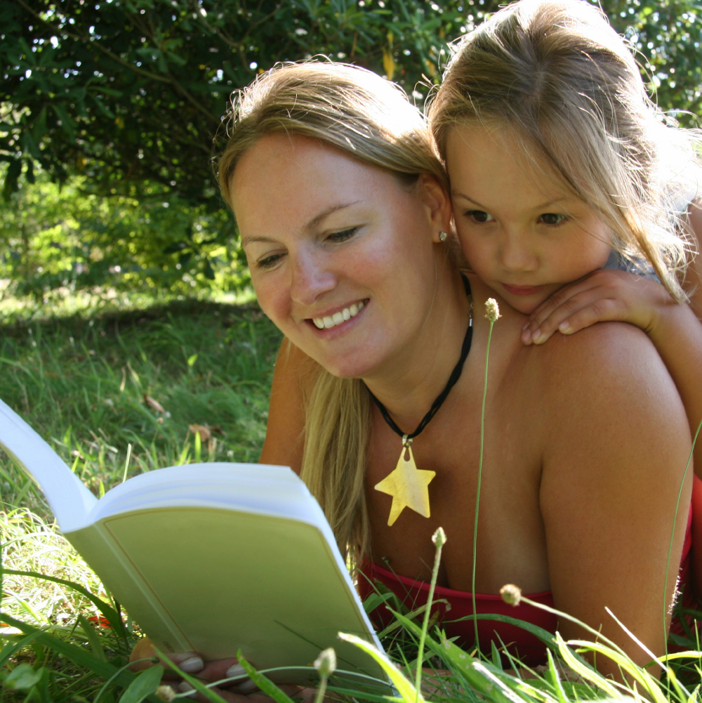 Child with adult reading a book
