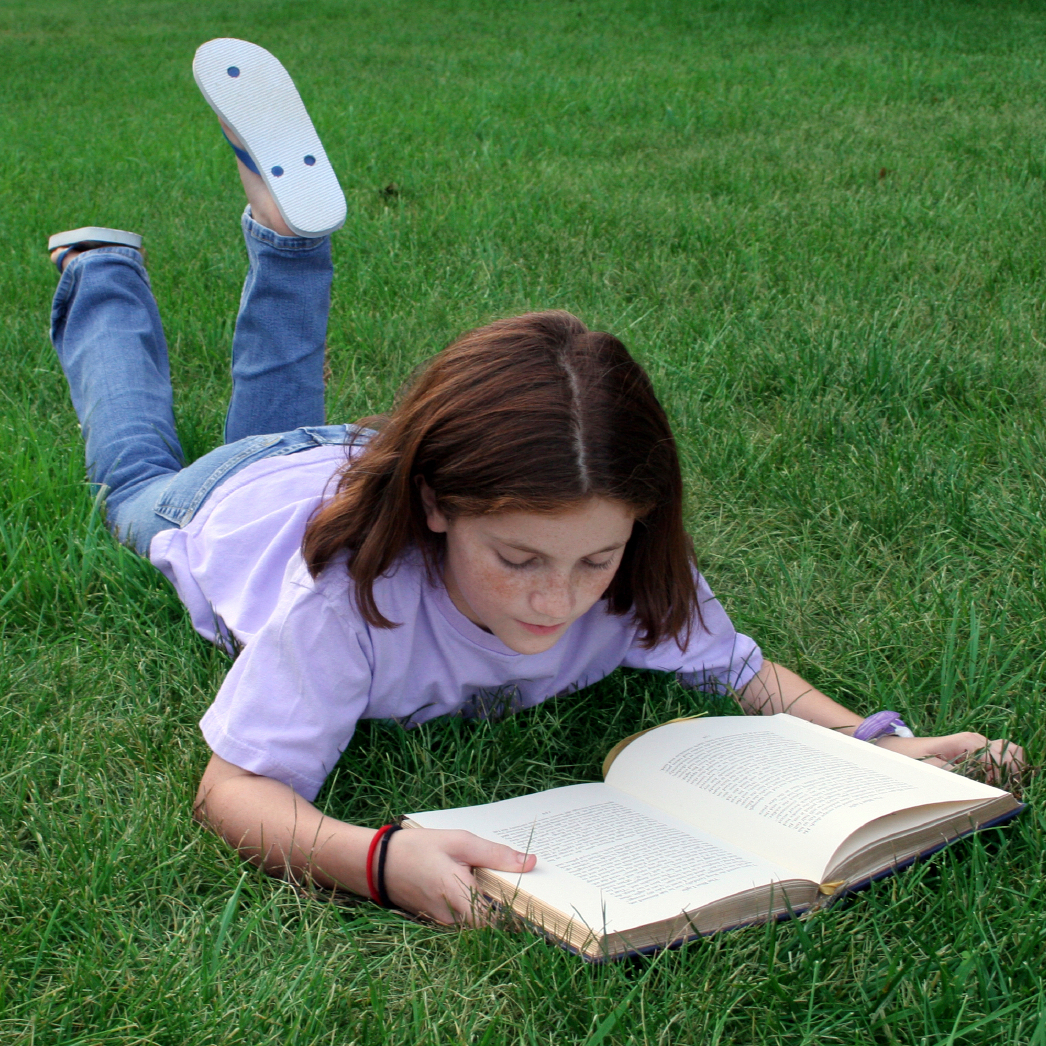 A young girl laying in the grass reading a book